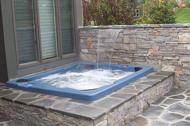 Vinyl Liner Pool with raised spa and sheer descent waterfall and bluestone patio in Saline MI by Legendary Escapes Pools (21)